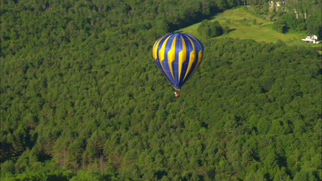 a hot air balloon drifts above a lush forest. - vermont stock videos & royalty-free footage