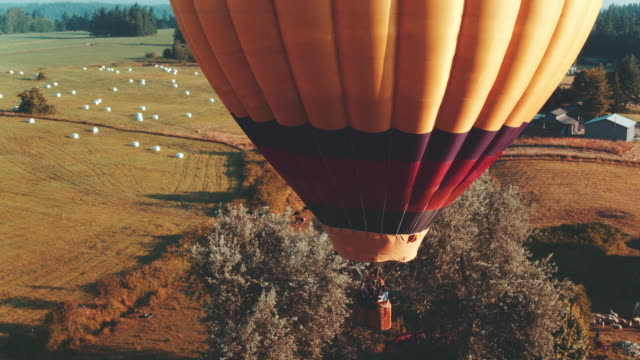 hot air balloon flies over farmland - hot air balloon stock videos & royalty-free footage