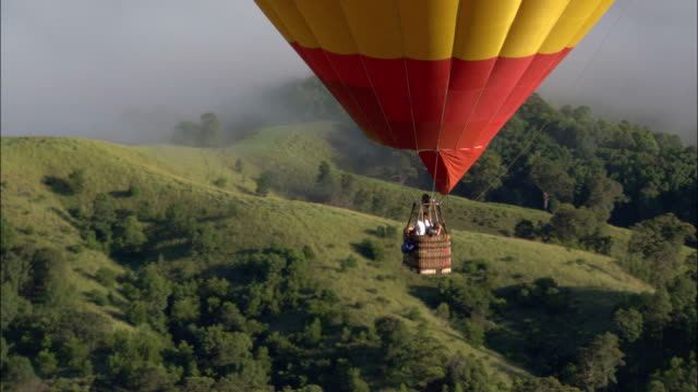 a hot air balloon flies over hillsides. - hot air balloon stock videos & royalty-free footage