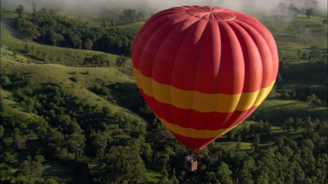 vídeos y material grabado en eventos de stock de a hot air balloon flies over hillsides. - globo aerostático