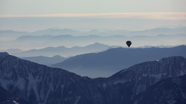 vídeos de stock e filmes b-roll de hot air balloon flight over austrian alps - balão de ar quente