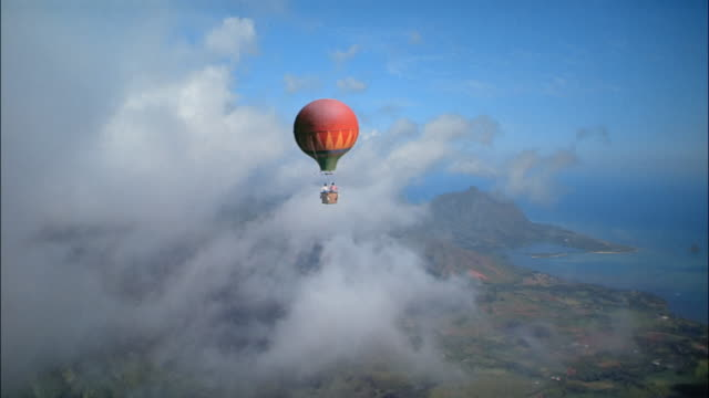 aerial hot air balloon floating above clouds and coastline - balloon stock videos & royalty-free footage