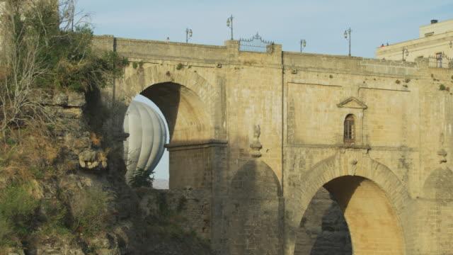 stockvideo's en b-roll-footage met hot air balloon floating behind arch at puente nuevo / ronda, malaga, spain - puente
