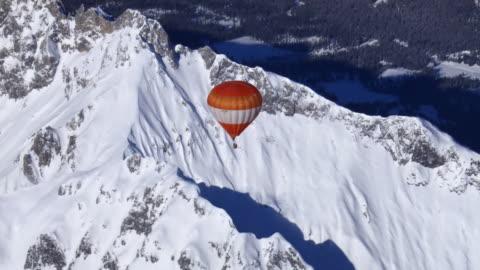 air to air, hot air balloon flying above snowy mountains, austria - air to air shot stock videos & royalty-free footage