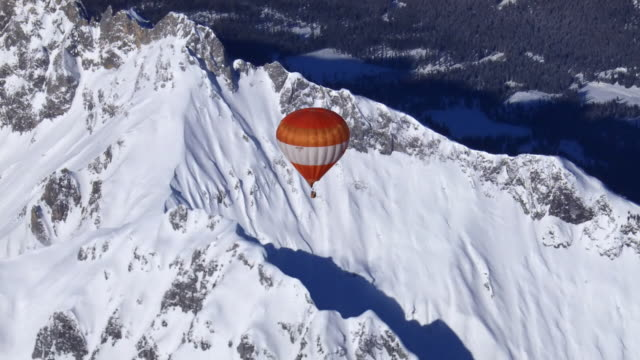 air to air, hot air balloon flying above snowy mountains, austria - air to air shot stock videos & royalty-free footage