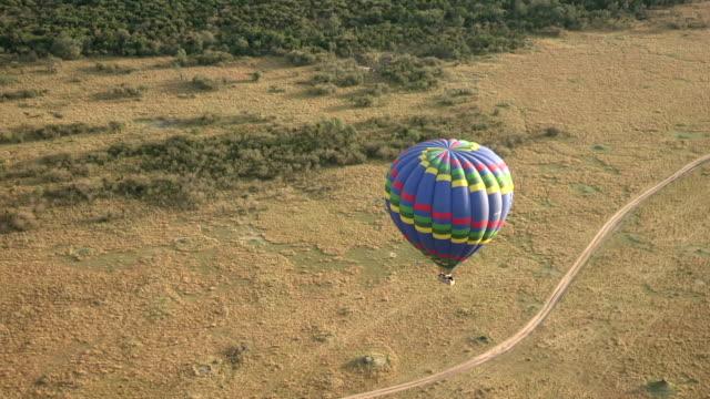 hot air balloon flying over masai mara game reserve. kenya - 熱気球点の映像素材/bロール