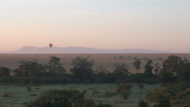 ws pov hot air balloon flying over wide grasslands of masai mara national park  audio / masai mara, rift valley, kenya - komplett stock-videos und b-roll-filmmaterial