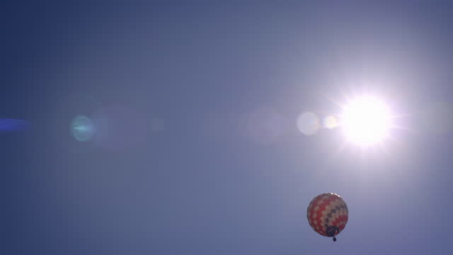 hot air balloon in blue sky with sun overhead - high up stock videos & royalty-free footage