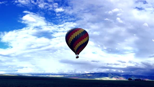 vídeos de stock e filmes b-roll de hot air balloon on a blue background - balão de ar quente