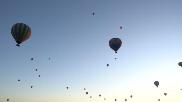 vídeos de stock, filmes e b-roll de balão de ar quente sobre um fundo azul - bexiga