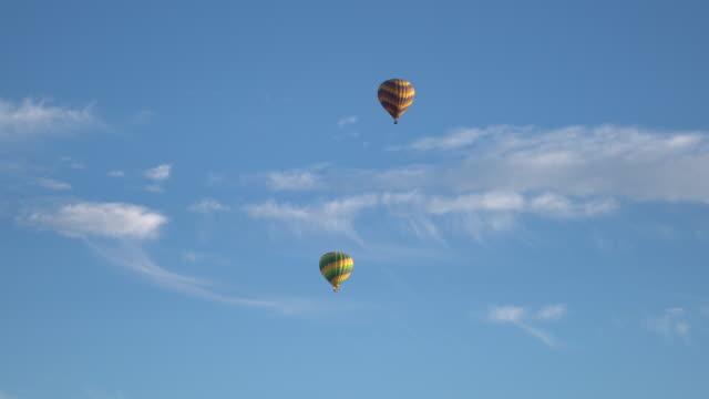 vídeos de stock, filmes e b-roll de balão de ar quente sobre um fundo azul - balão decoração