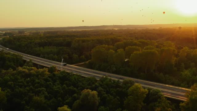 vídeos y material grabado en eventos de stock de aerial globos aerostáticos por encima de la carretera - multicóptero