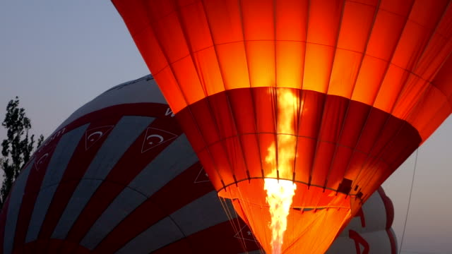 hot air balloons are preparing for flight over the goreme at cappadocia - cappadocia stock videos and b-roll footage