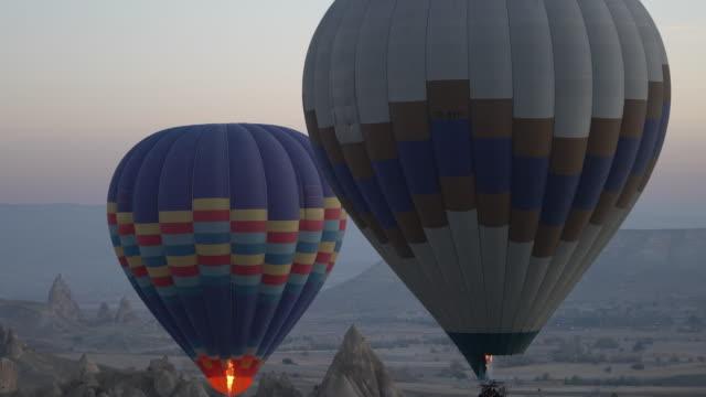 vidéos et rushes de ville de caverne de ballons air chaud en cappadoce, turquie - turquie