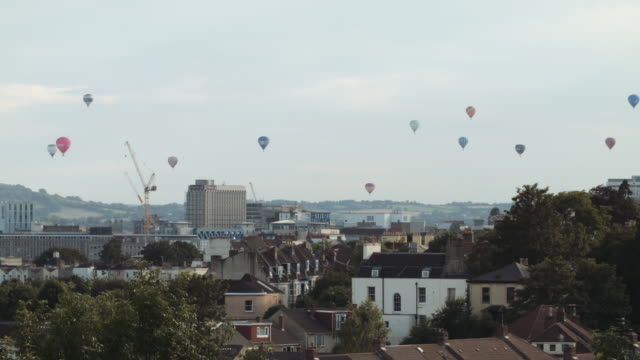 vídeos de stock, filmes e b-roll de hot air balloons crossing the skyline (bristol) 10 - festa do balão de ar quente