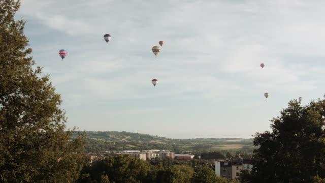 vídeos de stock, filmes e b-roll de hot air balloons crossing the skyline (bristol) 13 - festa do balão de ar quente