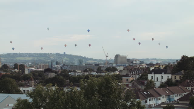 vídeos de stock, filmes e b-roll de hot air balloons crossing the skyline (bristol) 5 - festa do balão de ar quente