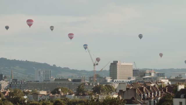vídeos de stock, filmes e b-roll de hot air balloons crossing the skyline (bristol) 9 - festa do balão de ar quente