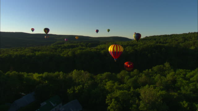 hot air balloons float over a vermont forest. - vermont stock-videos und b-roll-filmmaterial