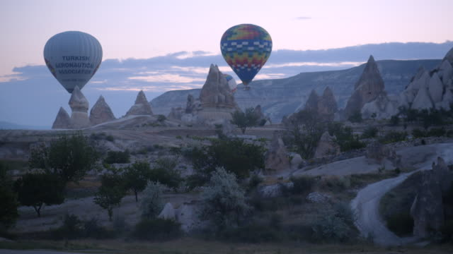 hot air balloons fly at dawn - cappadocia, turkey - anatolia stock videos and b-roll footage