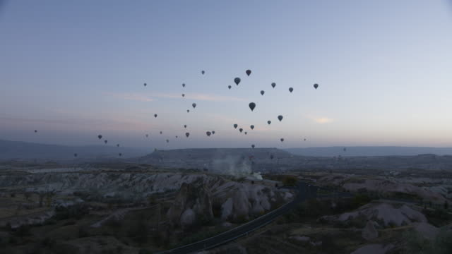Hot air balloons fly over Cappadocian desert at dawn, shot with a Red Epic-w