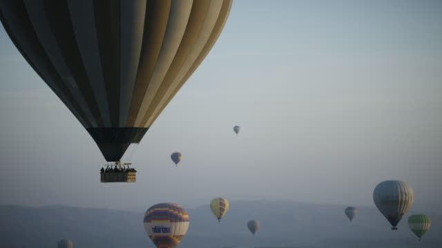 hot air balloons fly over cappadocian desert, shot with a red epic-w - turchia video stock e b–roll