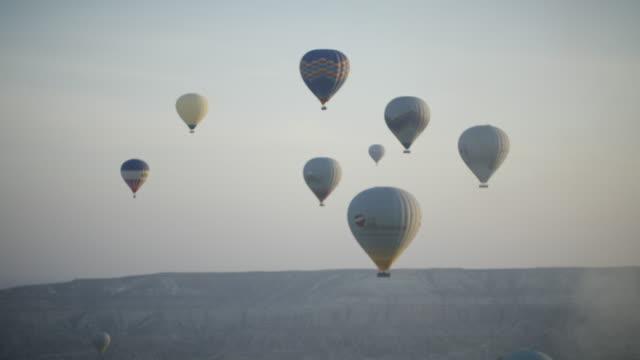 vidéos et rushes de hot air balloons fly over cappadocian desert, shot with a red epic-w - panoramique