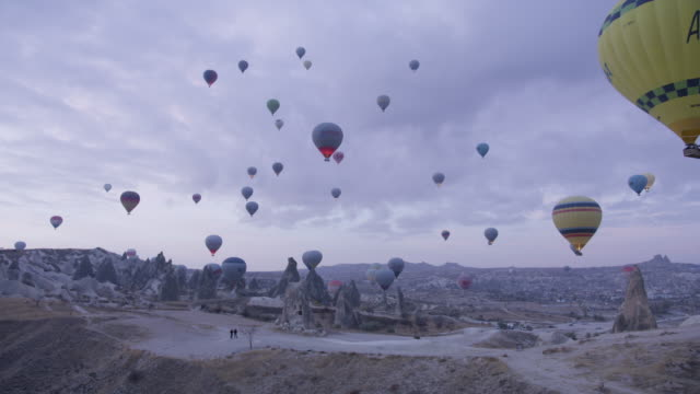 hot air balloons fly over cappadocian desert, shot with a red epic-w - cappadocia stock videos and b-roll footage