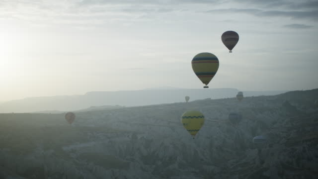 hot air balloons fly over cappadocian desert, shot with a red epic-w - anatolia stock videos and b-roll footage