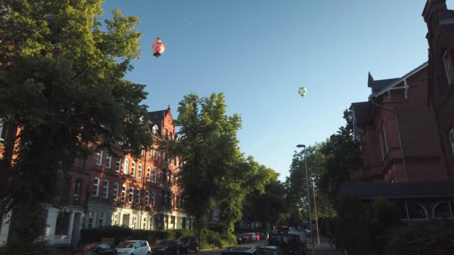 kiel schleswig holstein germany june 22 2019 hot air balloons fly over the kirchhofallee during the kieler woche blue sky trees heißluftballone... - tina terras michael walter 個影片檔及 b 捲影像