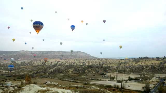 hot air balloons flying in red and rose valley in goreme in cappadocia in turkey - rock hoodoo stock videos & royalty-free footage