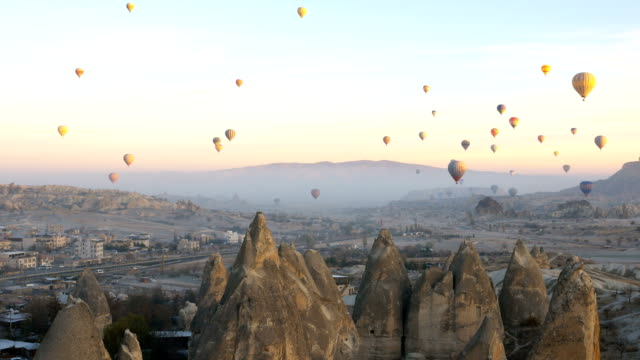 hot air balloons flying in red and rose valley in goreme in cappadocia in turkey - cappadocia stock videos and b-roll footage