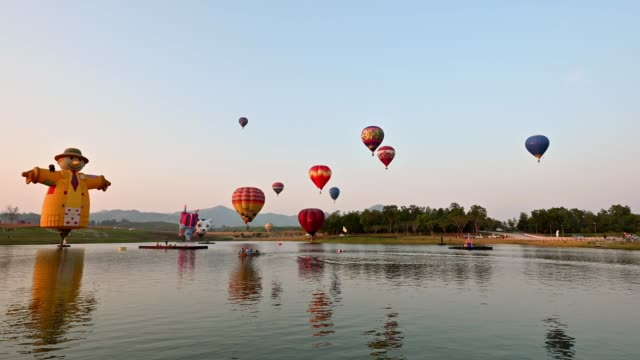 hot air balloons flying on lake in annual festival at chiang rai - rai stock videos and b-roll footage