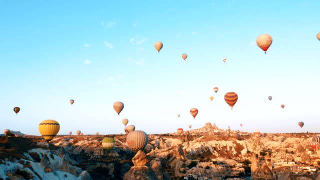 hot air balloons flying over the fairy chimneys with background uchisar castle at cappadocia - hot air balloon stock videos & royalty-free footage