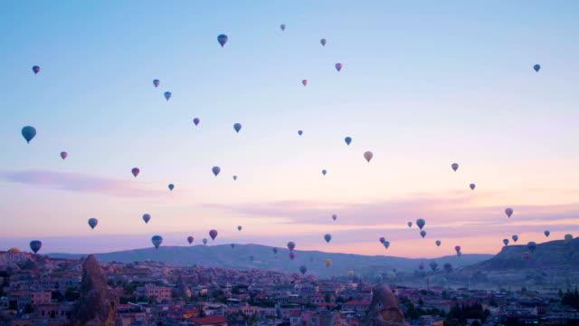 vídeos de stock, filmes e b-roll de balões de ar quente sobrevoando vales em göreme, capadócia, na turquia. - capadócia