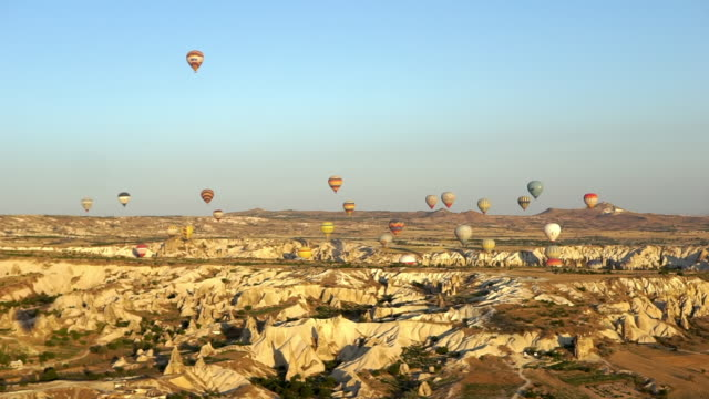 hot air balloons hover over white basalt hills at morning - cappadocia, turkey - basalt stock videos & royalty-free footage
