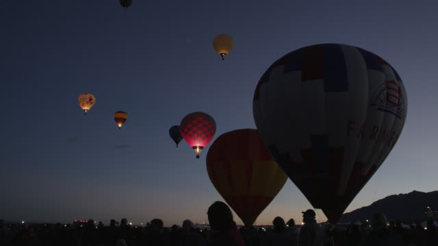 MS hot air balloons illuminating and flying at sunrise / Albuquerque, New Mexico, United States