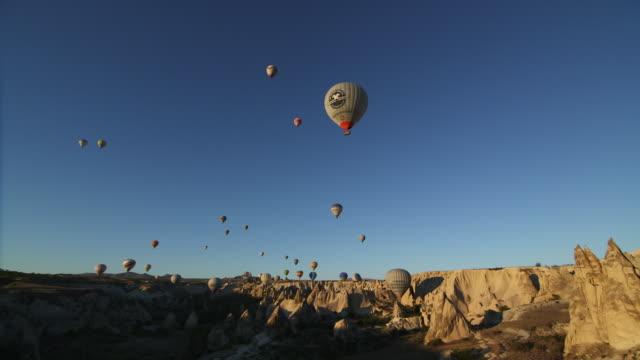 vídeos de stock e filmes b-roll de hot air balloons over love valley - wiese