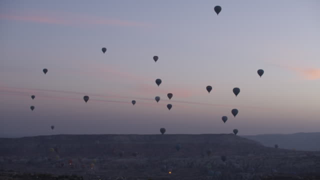 hot air balloons take off at sunrise in cappadocian desert, shot with a red epic-w - anatolia stock videos and b-roll footage