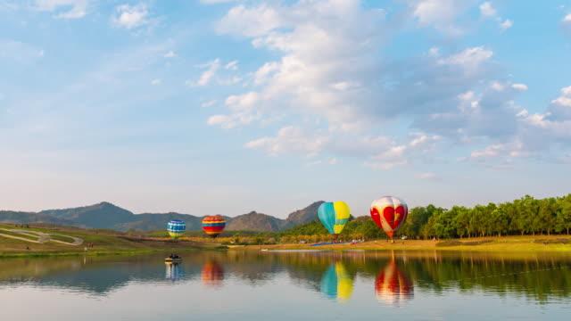 vídeos y material grabado en eventos de stock de aire caliente globos toma apagado alrededor del lago con cielo azul, video de lapso de tiempo - globo aerostático