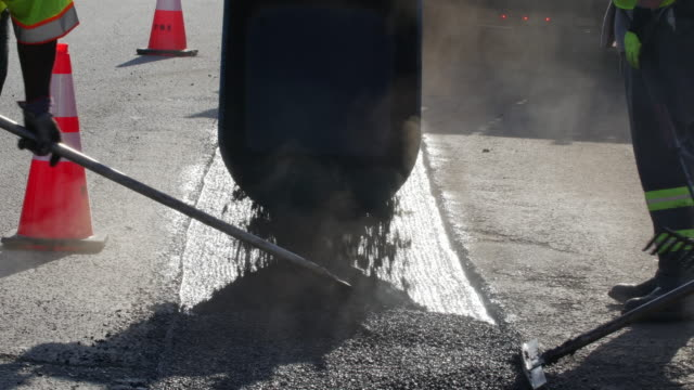Hot asphalt was poured and paved on the road pothole