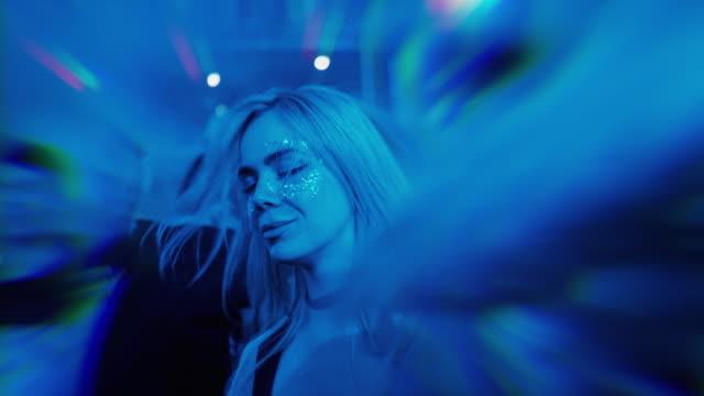 Hot blonde Mädchen mit Glitzer tanzen im Nachtclub