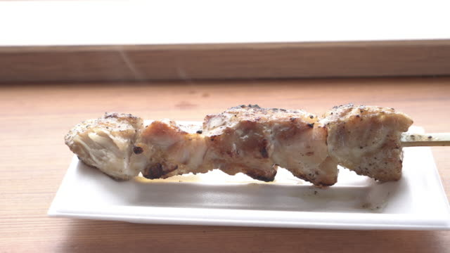 hot chicken stick grill in window light and smoke - cinque oggetti video stock e b–roll