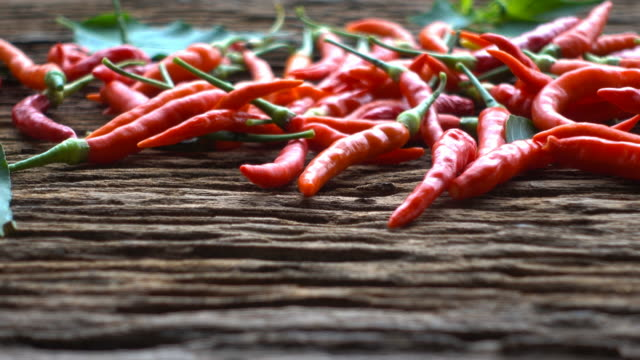 4k : hot chili on old wooden table in dolly shot - peperoncino video stock e b–roll