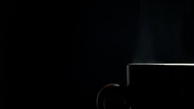 tasse heißen kaffee auf schwarzem hintergrund - cup stock-videos und b-roll-filmmaterial