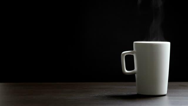 vídeos de stock e filmes b-roll de hot coffee cup on black background - chávena