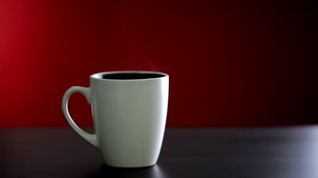 Hot coffee cup on red background
