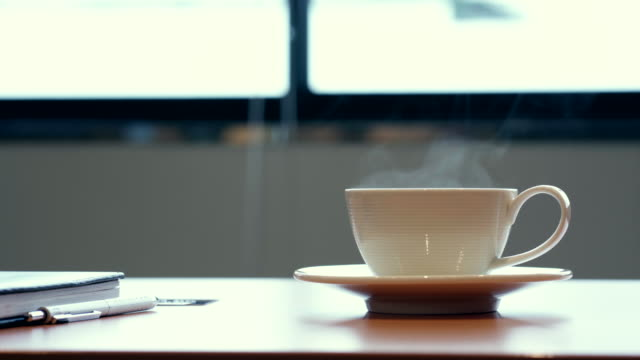 hot coffee cup on the table at the office. - tazza video stock e b–roll