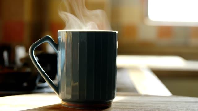 hot coffee cup steaming on table - tazza da caffè video stock e b–roll