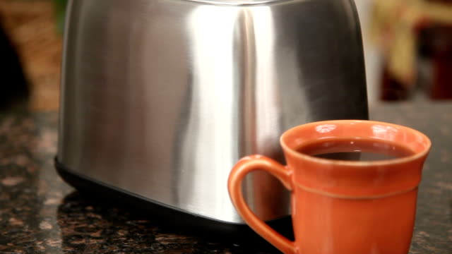 hot coffee  in cup leading  to toast popping in toaster - toaster appliance stock videos & royalty-free footage